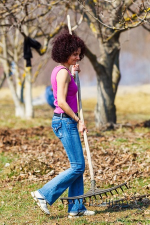 Young woman with a rake spring cleaning in a walnut orchard photo