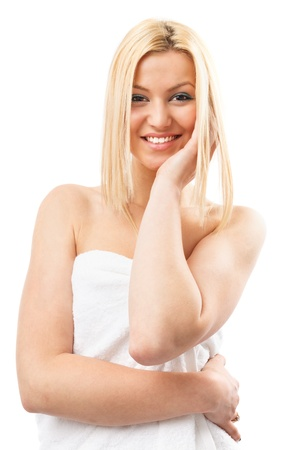 Beautiful young blond woman wrapped in spa towel, isolated on white photo