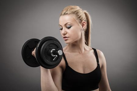levantando pesas: Mujer joven atl�tico hacer ejercicios con pesas