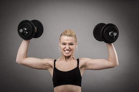 levantamiento de pesas: Mujer joven atlético hacer ejercicios con pesas