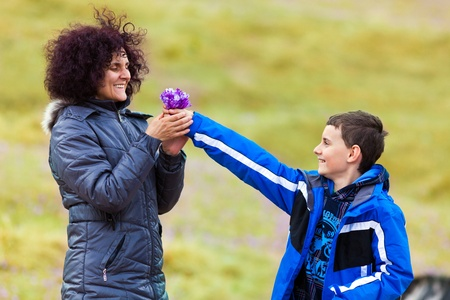 Son giving flowers to his mother, outdoor Stock Photo - 13220384