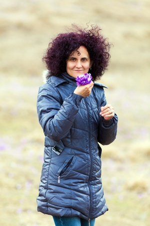 Candid portrait of a curly redhead woman picking crocus flowers in a meadow photo