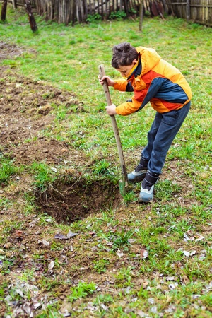 Boy digging on a grass field in the countryside Stock Photo - 13220243