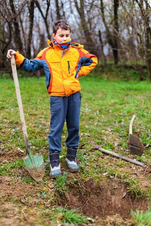 Boy digging on a grass field in the countryside photo