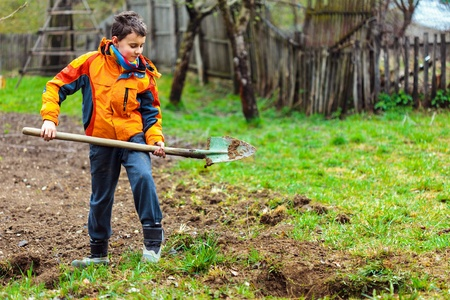 Boy digging on a grass field in the countryside Stock Photo - 13220361