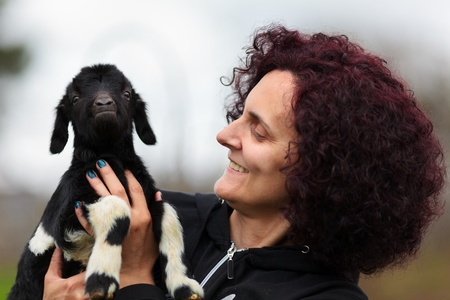 Closeup portrait of a young woman holding a baby goat outdoor photo