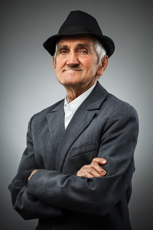 Studio portrait of a smiling old man with hat photo