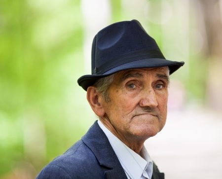 Closeup portrait of a senior man with hat outdoor