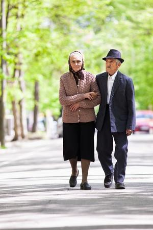 ancianos caminando: Senior pareja caminando al aire libre en el parque