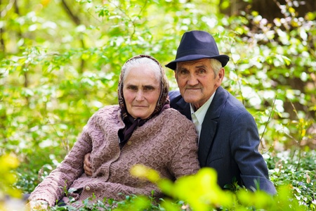 Senior couple sitting in grass in the forest, relaxing photo