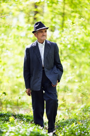 old farmer: Portrait of a senior man walking in the forest Stock Photo