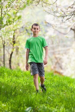 Full length portrait of a boy walking outdoor in a forest photo