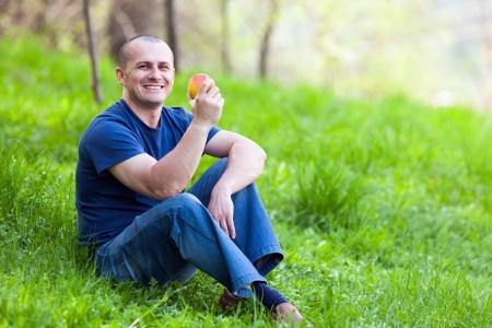 Jeune homme assis dans l'herbe et manger une pomme fraîche Banque d'images