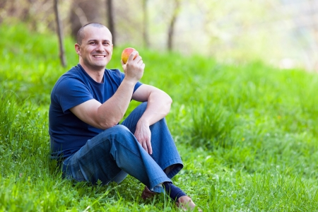 Young man sitting in grass and eating a fresh apple