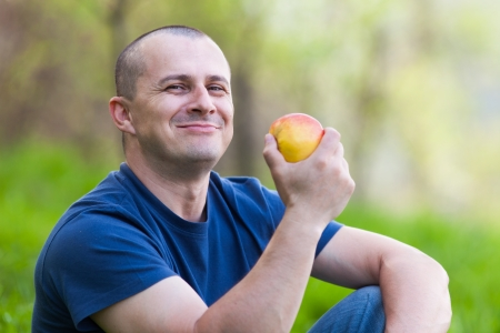1 man only: Young man sitting in grass and eating a fresh apple