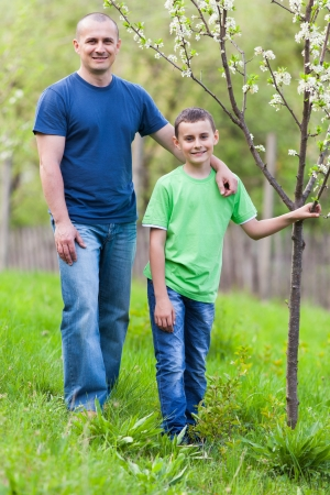 Happy father and son outdoor in an orchard photo