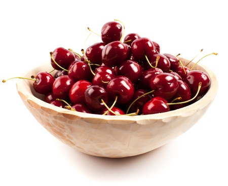 Red cherries in a carved wooden bowl isolated on white background Stock Photo - 15581136
