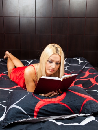 Glamorous blond young woman reading a book in bed photo