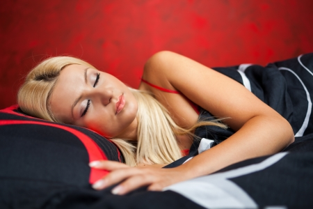 Gorgeous blond young woman lying in bed in red underwear Stock Photo - 15609931