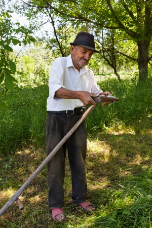 Senior rural man sharpening his scythe for mowing the grass photo