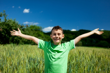 Happy boy in a wheat field with his arms stretched photo