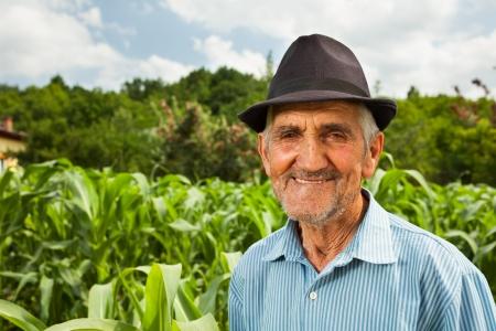 Retrato de un granjero mayor con un campo de maíz en el fondo, enfoque selectivo