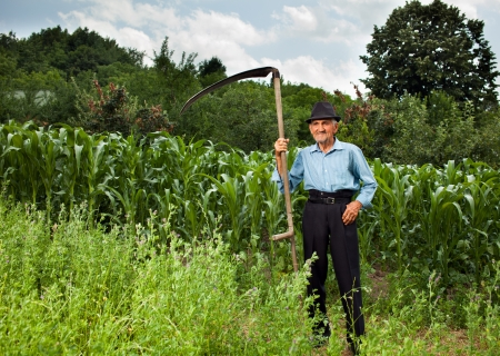 Senior farmer with scythe near a corn field having a break from work photo