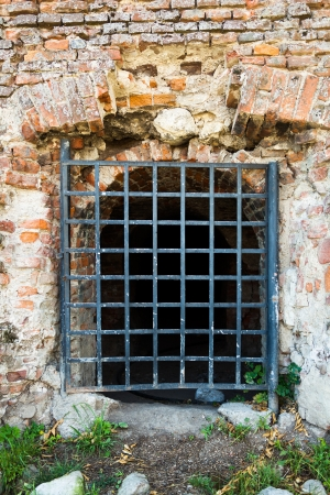 grates: Ancient brick wall with grates Stock Photo