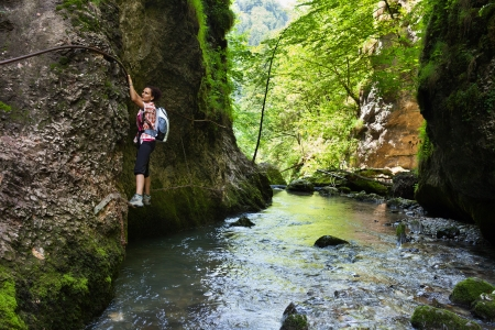Woman climbing mountain wall over a river in a canyon photo