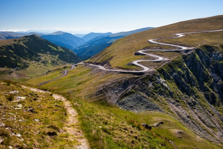 Landscape with a winding road and a trail on mountains photo