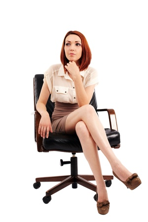 Young redhead businesswoman sitting in a chair isolated on white photo