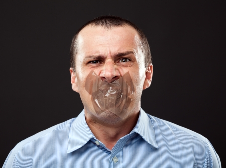 silenced: Conceptual image of a businessman with duct tape over his mouth