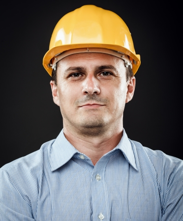 yellow hard hat: Young construction worker in hard hat on gray background