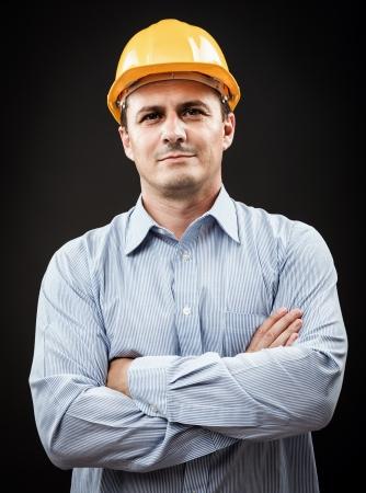 professions: Joven trabajador de la construcción en el sombrero duro en fondo gris