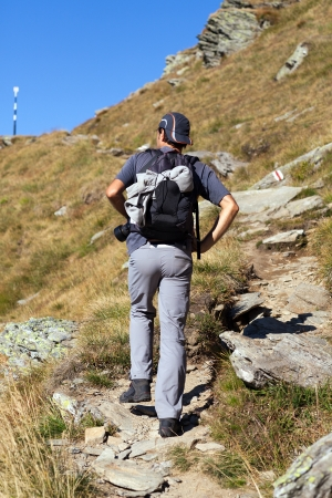 Young man with backpack hiking into the mountains photo