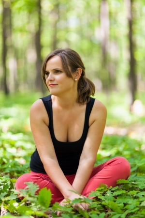 Young woman sitting in a forest, selective focus photo