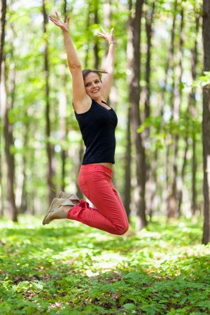 Young woman jumping for joy outdoor in the forest photo