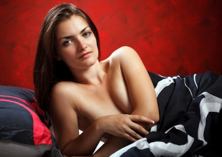 Studio portrait of a sensual brunette lying in bed photo
