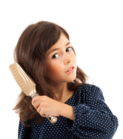 Closeup portrait of a little girl brushing her hair isolated on white