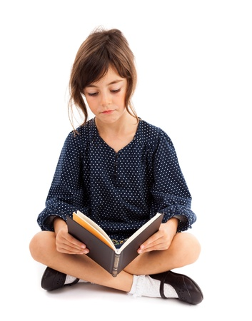 crossed legs: Full length portrait of a little girl reading while sitting with crossed legs Stock Photo