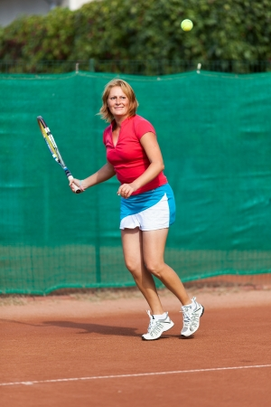 dross: Full length portrait of a young woman playing tennis on a dross field