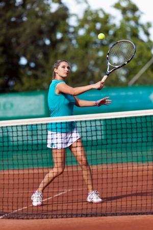 Portrait en pied d'une jeune femme jouant au tennis sur un terrain de scories