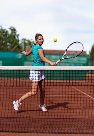 backhand: Retrato de cuerpo entero de un jugador de tenis de la mujer hermosa preparado para un golpe de rev�s