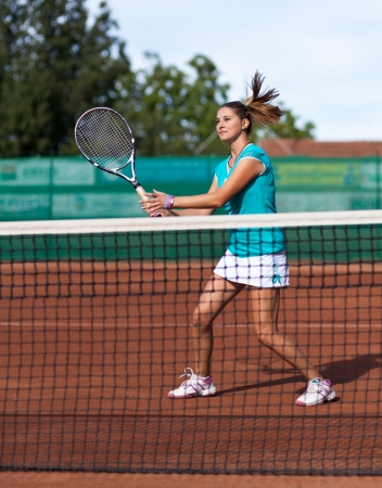 tennis skirt: Full length portrait of a young woman playing tennis on a dross field