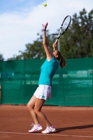Portrait en pied d'un joueur de tennis belle femme purge une balle de tennis