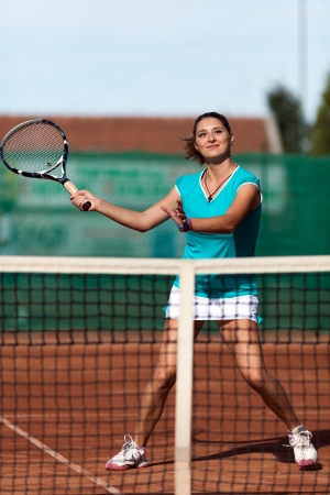 Full length portrait of a young woman playing tennis on a dross field photo