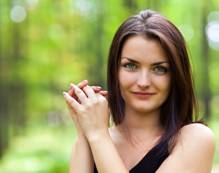 Closeup portrait of a gorgeous woman stading with hands near the face in the woods