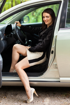 Portrait of a beautiful young woman with new car photo