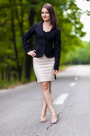 Full length portrait of a young businesswoman standing on the road with hand on hip and crossed legs photo
