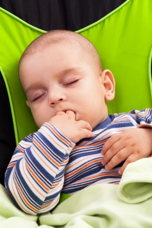 Cute toddler boy sleeping in a baby lounger, sucking his fingers Stock Photo - 15895229